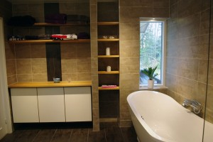 Stort badrum med kakel o klinkers i varma färger . Trädetaljer i oljad ek.