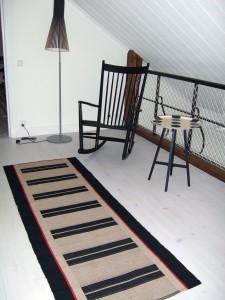 Loftgång en trappa upp med luftigt smidesräcke.